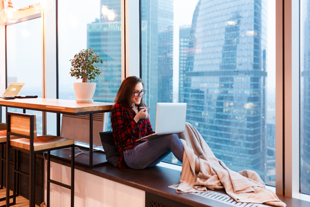 Cute young woman outsourcing designer working in creative studio sitting under blanket with mug of coffee and working at the computer on background of large window overlooking the skyscrapers Stock fotó