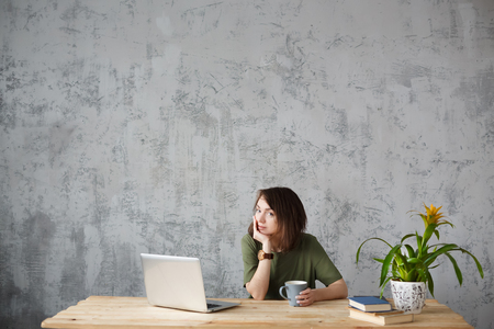 Portrait of young positive beautiful woman designer working in large company during coffee breaks sitting at table with laptop. looks happily directly into camera.Copy space