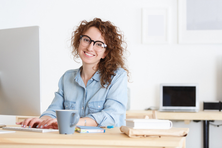 Portrait of talented female marketing expert thinking over ideas concerning business strategy. Looking and smiling at the camera during working day.