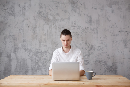 Business concept. Young charming man is focussed looks at the laptop while working at table on gray background. works on new startup project, makes internet researches, analyzes data. Place for text or ads