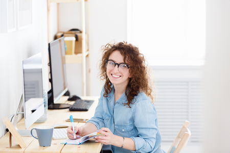 Indoor shot of young female startupper or cheerful caucasian freelancer work in light office, has good mood, ooks with pleasant smile in camera. People, emotions,business