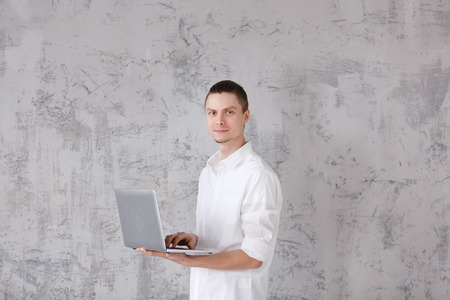 Portrait of positive young man holding laptop and broadly smiling looking in the camera on gray vintage wall background. Copyspace