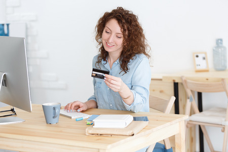 Attractive young female with red hair making payment while shopping online at work place, entering data online payment form while ordering shopping