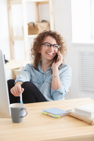 Attractive successful woman sits at desk, works remotely at home, has phone conversation with colleague or business partner. Beautiful creative manager has happy expression.