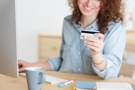 Online shopping. Cropped shot of unrecognizable caucasian female in blue shirt keyboarding on laptop pc, holding credit card,paying bills online Foto de archivo