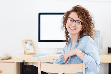 Portrait of positive cheerful young Caucasian female freelancer wearing stylish glasses and casual shirt sitting at desk after hard working day, smiling at the camera.