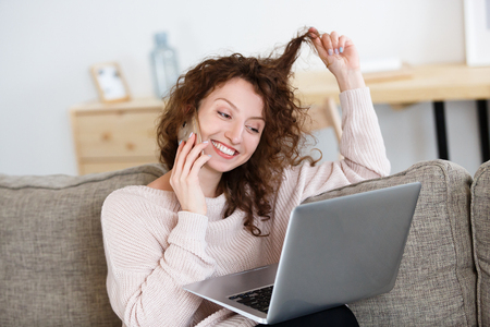 Cheerful European woman has pleasant conversation on smart phone, enjoys online communication on laptop in cozy home. Communication concept