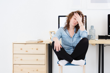 Unhappy disappointed woman with stubble covers face with hand has much work and sleppless night. Stress, fatigue overwork.