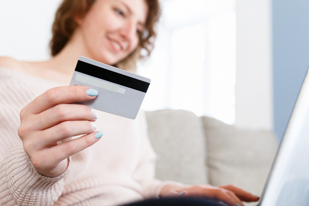 Close up shot of caucasian womans hands holding credit card, using laptop fop paying online or for paying bills