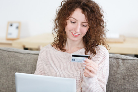 Cropped shot of caucasian female in cozy sweater sitting at home keyboarding on laptop pc, holding credit card, making payment while shopping online.