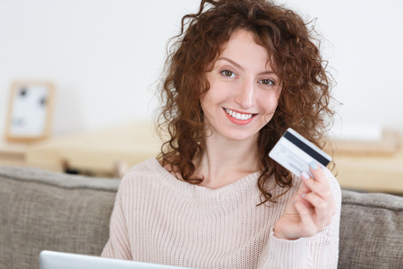 Close up portrait attractive European woman looking at camera with happy expression,surfing websites while shopping online, uses online banking. People and ecommerce concept Foto de archivo