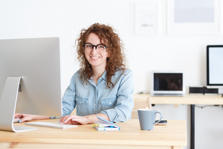 Attractive female freelancer works remotely at home uses wireless internet connection,sits at work place,surrounded by computers and gadgets