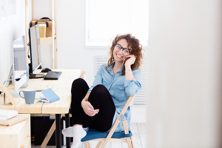 Charming glad caucasian female freelancer sitting at working desk at home and doing remote job. Successful marketing expert holds smart phone as communicates remotely with partners