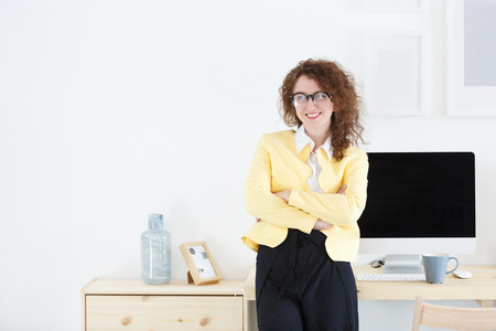 Attractive young pensive woman engineer in formal clothes stands at the desk with computer and electronic gadgets in white office during break at work.