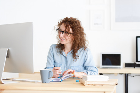 Positive cheerful young Caucasian female freelancer in round glasses uses wireless internet connection, works remotely at home