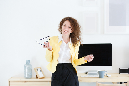 Stylish business lady looking and smiling at camera during working day. Attractive female designer standing at her workplace surrounded by gadgets and computer, being happy