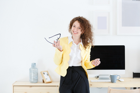 Horizontal portrait of gorgeous beautiful young successful female manager in white modern office stands at the desk and drinks coffee during break of working day. Gets positive emotions from flirting with colleagues at work