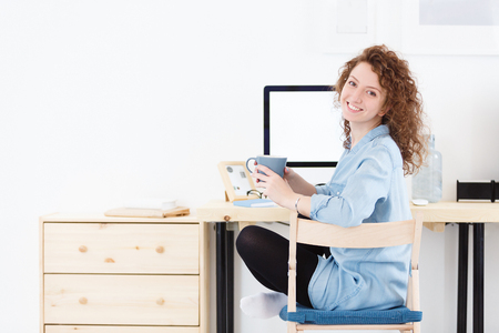 Positive cheerful young Caucasian female programmer or startupper looking and smiling at the camera during small break,downloads program at laptop computer