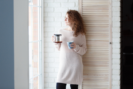 Beautiful caucasian woman with curly red hair drinking coffee,standing by the big window, enjoying a quiet cozy evening at home