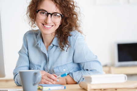 Cropped shot of Positive cheerful young caucasian female freelancer works in good mood at laptop computer in creative studio