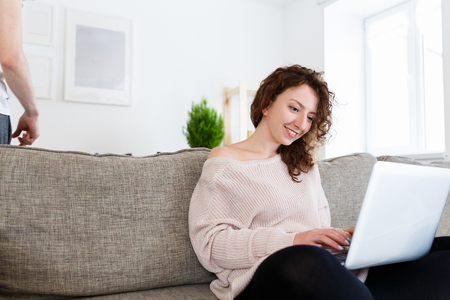 Happy female copywriter writes ideas on laptop, uses computer for creating new article in fashion magazine.