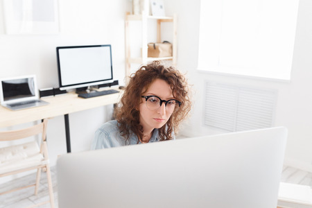 Indoor shot of serious concentrated business lady reads information on laptop computer, surfes internet in modern office