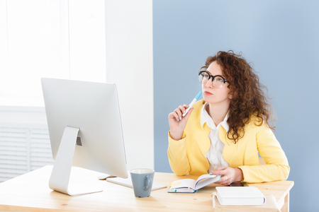 Serious hard working pleasant female business woman generates business ideas, works in office, looking aside with concentrated expression Banco de Imagens