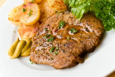 steak of pork with fried potato and salad