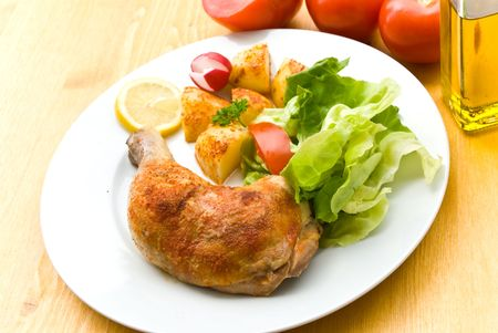 Fried chicken with fried potatoes, and lettuce,tomato,radish. photo