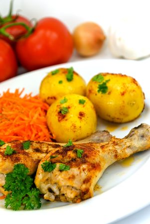 chicken legs with baked potato,salad of carrot photo