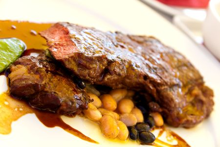 baked beans: Sirloin strip Steak with green Beans ,vegetables and savory sauce Stock Photo