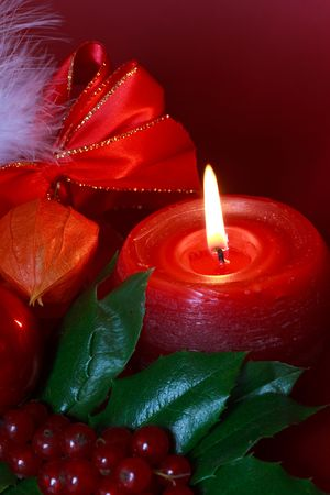 chinese holly: Green christmas wreath decorated with holly,red burning candle,ribbon Stock Photo