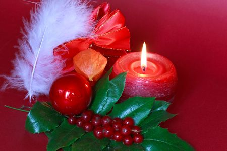 chinese holly: Green christmas wreath decorated with holly,red burning candle Stock Photo
