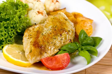 Grilled chicken breasts on a plate with fresh vegetables Stock Photo