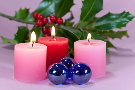 shinning light: christmas decoration with candle light,holly leaves and berries