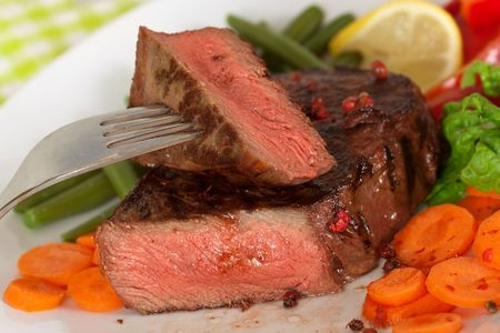 roast beef: New York Steak- meat on Green Beans,Carrot,Pepper and green salad over plate Stock Photo