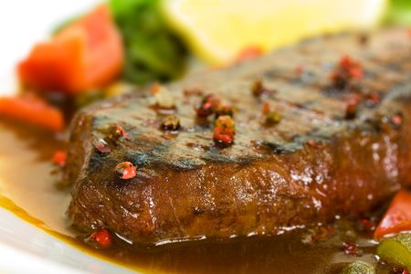 New York Steak- meat on Green Salad,Red Bell Pepper and Capers over plate - on Sauce Stock Photo