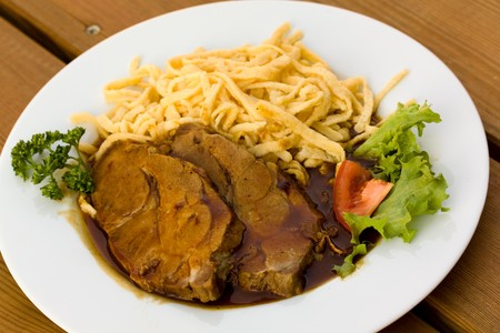swabian: Roast of Pork with Sauce,and spaetzle , type of South German pasta dish Stock Photo