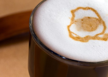 frothy:   freshly poured coffee with frothy milk, focus on bubbles