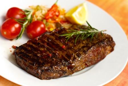 bistecche: grande bistecca di striscia di new york, alla griglia, con insalata  Archivio Fotografico