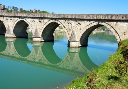 mehmed: Old,Famous bridge on the Drina in Visegrad, Bosnia and Herzegovina, on a hot summer day.  Stock Photo