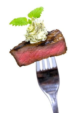 Gourmet Time,piece of a grilled steak with herb butter on a fork,isolated on white  Stock Photo - 10675624