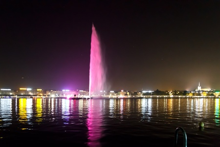 The famous Jet dEau fountain in Geneva by Night, Switzerland with tourists