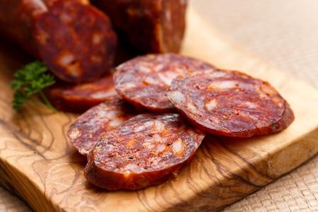Spanish chorizo sausage with parsley on rustic board Stock Photo