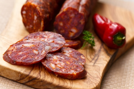 Spanish chorizo sausage with parsley on rustic board photo