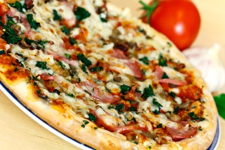 ham, mushroom and vegetable pizza and tomato at the back Stock Photo - 11234092