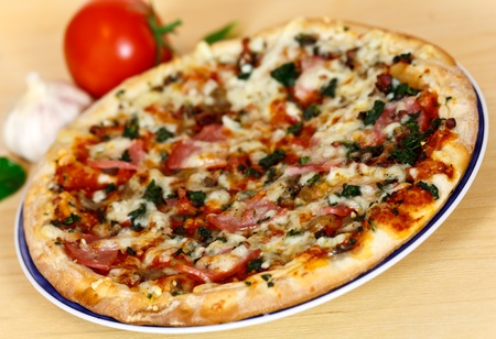 ham, mushroom and vegetable pizza and tomato at the back photo