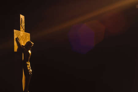 Jesus on the cross, lit by beam of light with other worldly flare