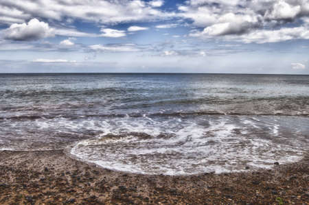 Gentle waves on shore with sea, horizon and luffly clouds. HDR image
