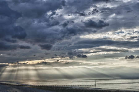 Suns rays bursting through clouds on sea, at near sunset. Breakwater and beach in foreground. HDR image